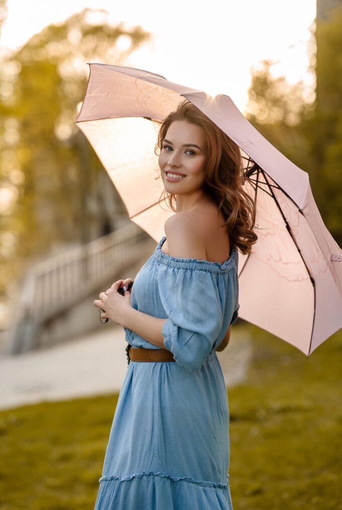 Naine vihmavarjuga suvel vanalinnas loven